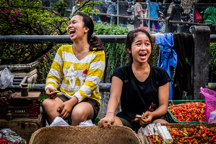 Two sisters laughing in Dempasar market