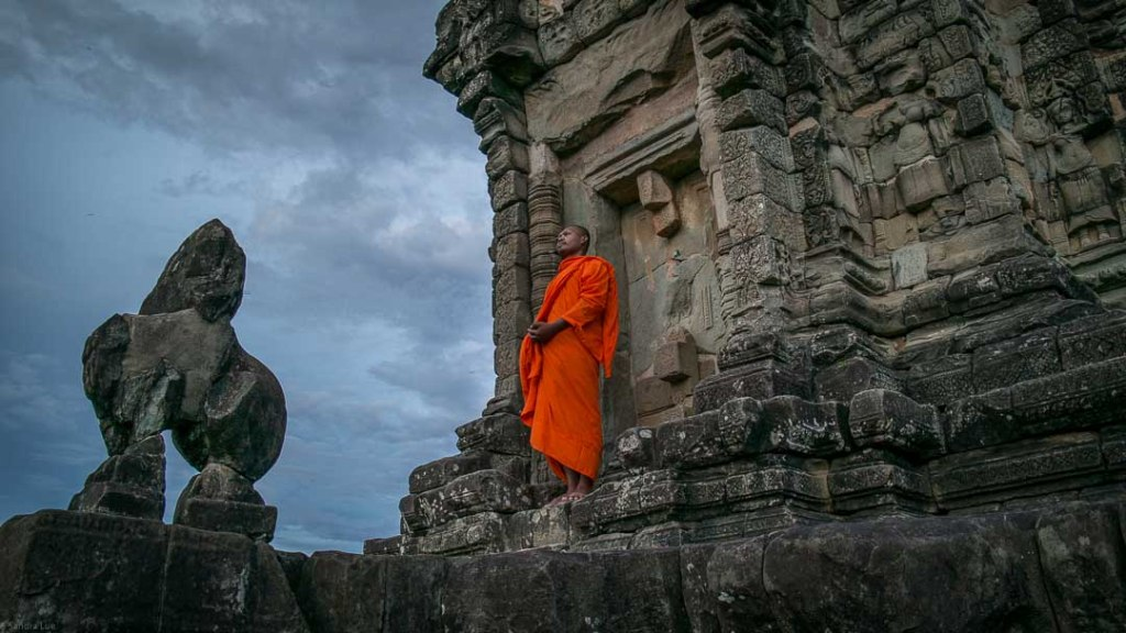 Buddhist monk on steps of Angkor temple in Siem Reap, Cambodia